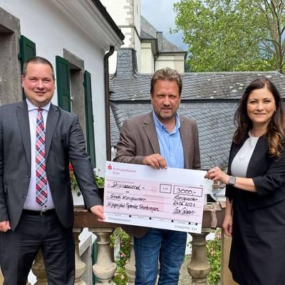 Theo Thiemann und Lisa Limmer von der Kreissparkasse Köln überreichen Bürgermeister Lutz Wagner den symbolischen Scheck in Höhe von 3000 EUR