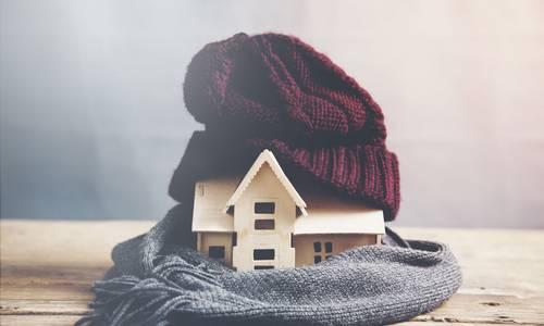 Symbolbild: Modell eines Holzhauses, das in einer Mütze und einem Schal eingewickelt ist